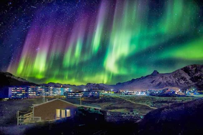 Una fantastica aurora boreale su una cittadina.