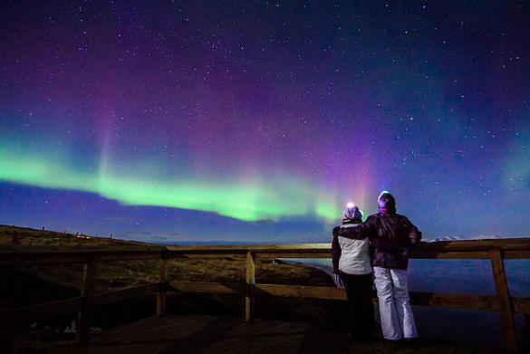 Una coppia guarda la stupefacente aurora boreale.