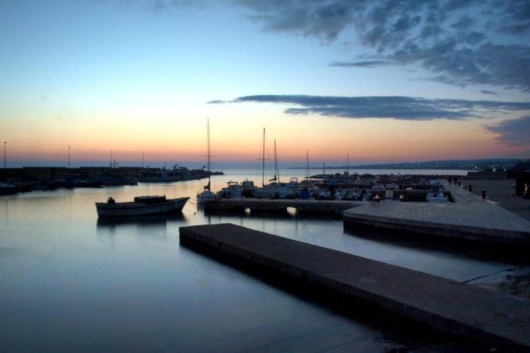 Foto lunga esposizione al tramonto in un porto.