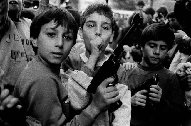 Foto di Letizia Battaglia, bambino con pistola giocattolo.